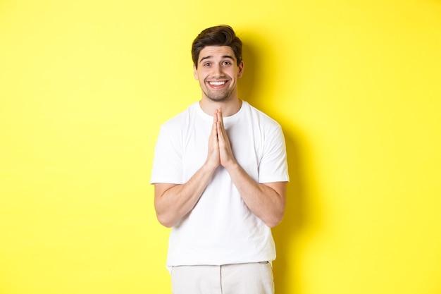 Hoopvolle man die om hulp vraagt, om gunst smeekt, iets nodig heeft en glimlacht, staande over een gele achtergrond.