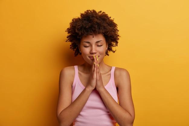 Hoopvolle mooie vrouw drukt de handpalmen samen in gebed, gelooft in welzijn, heeft een groot geloof, draagt een casual vest, sluit de ogen, blijft kalm, geïsoleerd over gele muur. mogen mijn dromen uitkomen.