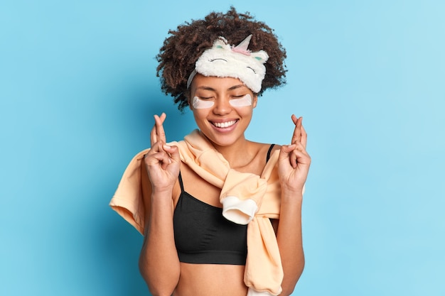 Hoopvolle mooie vrouw kruist vingers bidt voor beter voordat ze gaat slapen glimlacht zachtjes sluit ogen gekleed in pyjama ondergaat huidverzorgingsprocedures geïsoleerd over blauwe muur