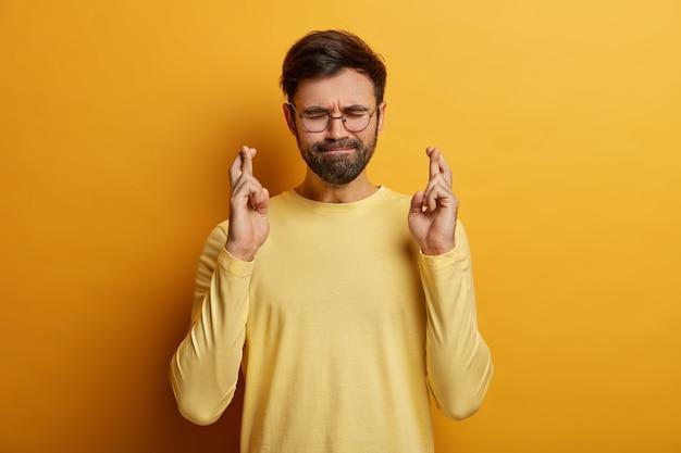 Hoopvolle ongeschoren man kruist vingers voor geluk, drukt lippen, heeft ogen dicht, bidt voor een beter leven, wacht op resultaten, draagt bril en gele trui, staat binnen. monochroom. hand teken