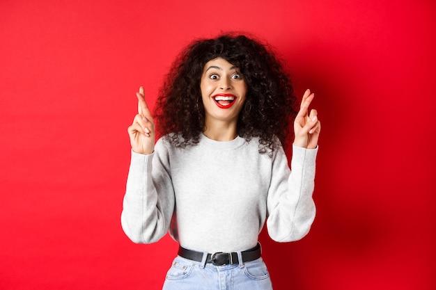 Hoopvolle opgewonden vrouw die een wens doet, vingers kruist voor geluk en verbaasd glimlacht naar de camera, biddend voor een droom die uitkomt, wachtend op resultaten, rode achtergrond