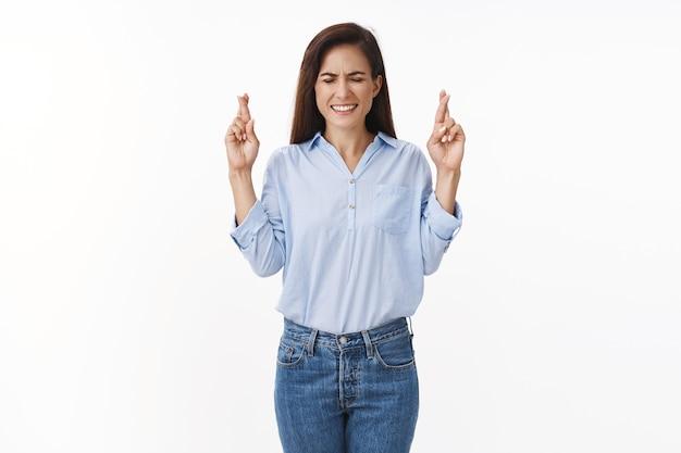 Hoopvolle optimistische intense volwassen vrouw wil graag winnen, ogen dicht op elkaar klemmen, focus op droom, vingers gekruist veel geluk, smeken, bidden wens komt uit, anticiperend op positief resultaat
