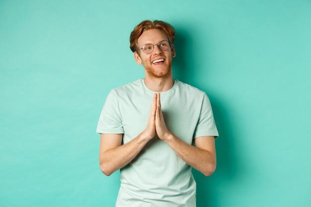 Hoopvolle roodharige man met baard, bril en t-shirt, hand in hand in namaste of pleit gebaar en kijkend naar rechts, glimlachend en bedankend, staande over turkooizen achtergrond.