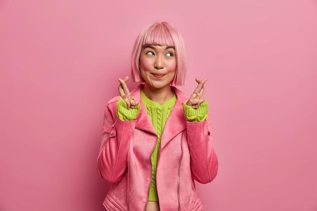 Hoopvolle rozeharige aziatische vrouw kruist vingers voor geluk gelooft in iets moois geconcentreerd opzij draagt bedachtzaam stijlvol jasje.