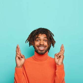 Hoopvolle vrolijke man met dreadlocks houdt de vingers gekruist, gelooft in geluk, glimlacht breed, draagt een oranje coltrui, geïsoleerd op blauwe achtergrond, kopieer ruimte boven