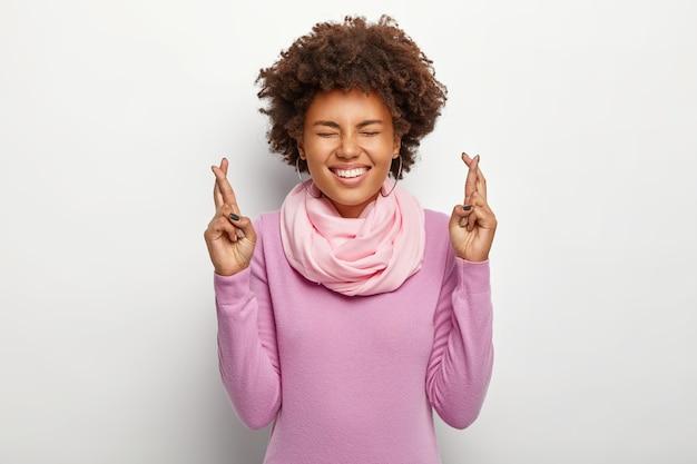 Hoopvolle vrouw met intens krullend haar steekt haar vingers op, gefocust op dromen, verwacht positief resultaat, glimlacht breed, draagt paarse outfit, staat tegen witte muur, smeekt om geluk