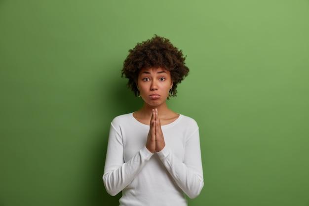 Hoopvolle vrouw smeekt haar handpalmen tegen elkaar, smeekt met een ondeugende en smekende grimas, vraagt om hulp of verontschuldiging, draagt een witte trui, geïsoleerd op een groene muur. geef me alsjeblieft nog een kans