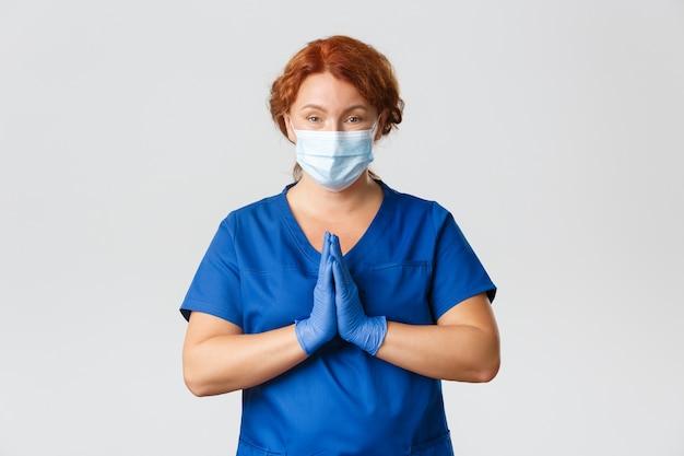 Hoopvolle vrouwelijke arts, roodharige arts of verpleegster die om hulp vraagt, hand in hand in pleidooi, gezichtsmasker en handschoenen draagt, blijf alsjeblieft thuis