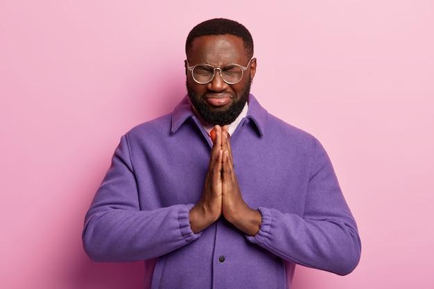 Hoopvolle zwarte man houdt beide handen tegen elkaar gedrukt in gebedgebaar, gelooft in geluk