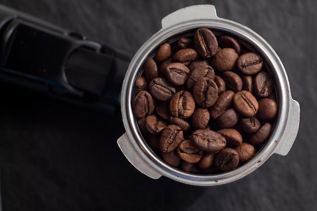 Hoorn met koffiebonen. koffiemachine filterhouder met koffiebonen op zwart leisteen bord.
