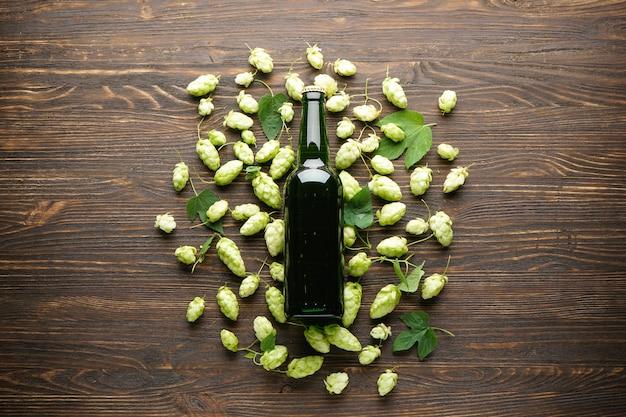 Hop en light bier in een fles op een houten ruimte, bovenaanzicht