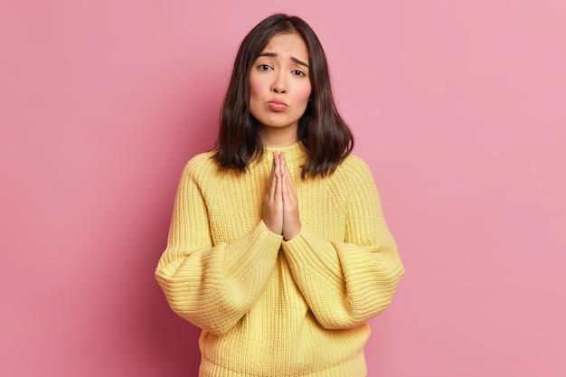 Hopeloze brunette vrouw houdt handpalmen tegen elkaar gedrukt en kijkt smekend om gunst vraagt om nog een kans draagt gele trui met lange mouwen
