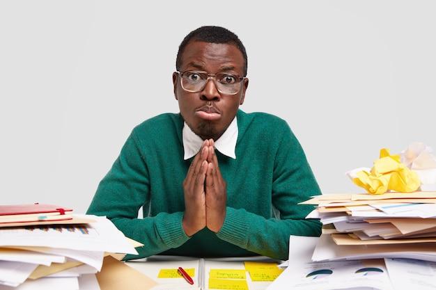 Hopeloze zwarte student weet niet hoe hij een taak moet uitvoeren, vraagt en smeekt groepsgenoot om hulp, houdt de handpalmen tegen elkaar gedrukt, heeft medelijden met gezichtsuitdrukking