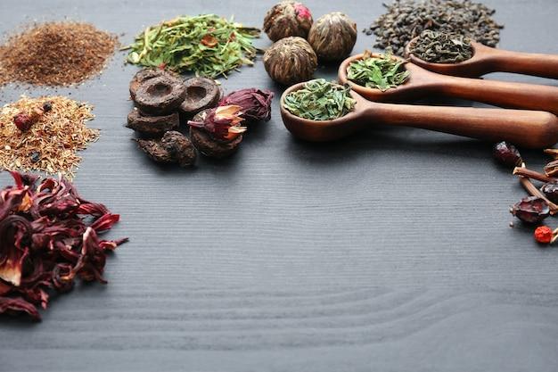 Hopen verschillende droge thee op grijze houten tafelruimte, close-up
