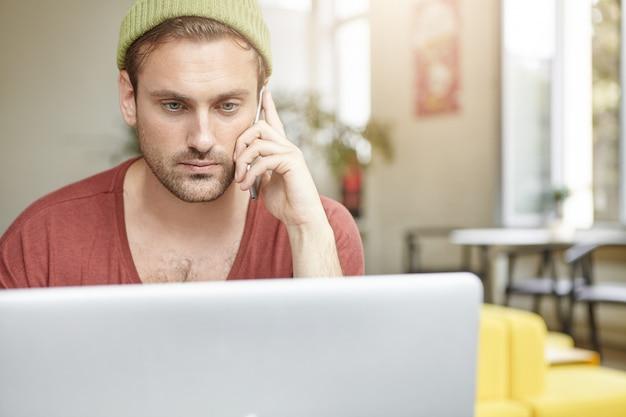 Horizonatal portret van ernstige bebaarde man heeft een oproepgesprek, zit voor generieke laptop