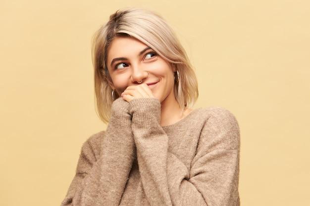 Horizontaal beeld van aantrekkelijke charmante jonge blanke vrouw met neusring, ronde oorbellen en stijlvolle warme beige trui hand in hand samen en wegkijken met mysterieuze glimlach