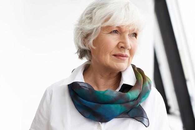 Horizontaal beeld van aantrekkelijke modieuze gepensioneerde vrouw, gekleed in een wit overhemd en een elegante zijden sjaal die thuis dagdromen,
