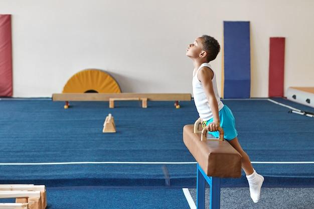 Horizontaal beeld van bekwame afro-amerikaanse jongensturner die voor artistieke gymnastiekcompetitie voorbereidingen treffen