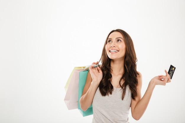 Horizontaal beeld van blije vrouw met veel in hand aankopen doen die gebruikend creditcard gebruiken, die over de witte ruimte van het muurexemplaar wordt geïsoleerd