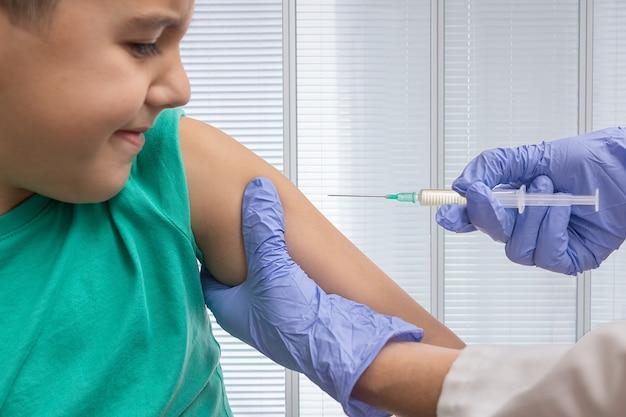 Horizontaal beeld van de handen van een verpleegster met handschoenen die een spuit houden om een kind te vaccineren
