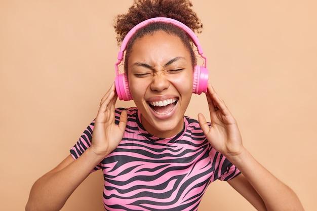 Horizontaal beeld van dolblije jonge vrouw glimlacht breed geniet van aangename melodie houdt handen op koptelefoon heeft een vrolijke stemming gekleed in gestreept roze en zwart t-shirt poseert binnen