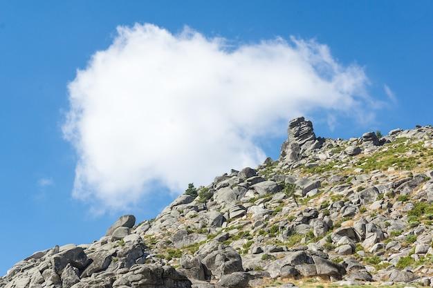Horizontaal beeld van een rotsachtige berghelling die een diagonaal vormt met de blauwe hemel met een witte wolk