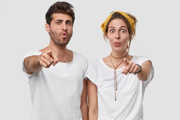 Horizontaal beeld van emotioneel verrast blanke ongeschoren man en dame wijzen rechtstreeks met wijsvingers, hebben een verbaasde gezichtsuitdrukking