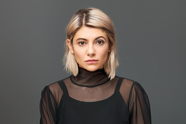 Horizontaal beeld van geweldige jonge vrouw met blonde bob kapsel en artistieke make-up met witte kristallen rond haar oog poseren geïsoleerd in trendy blouse, met zelfverzekerde blik
