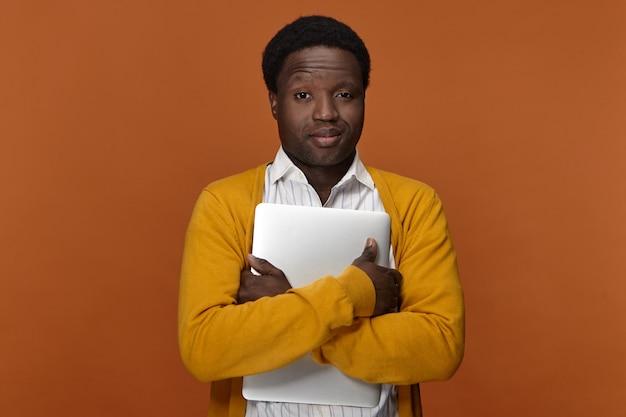 Horizontaal beeld van succesvolle zelfverzekerde knappe jonge afro-amerikaanse zakenman die draagbare computer omhelst die tevreden gelaatsuitdrukkingen heeft tevreden gesteld, glimlachen, genietend van elektronisch apparaat