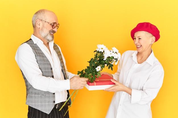 Horizontaal beeld van verlegen, onhandige grootvader met grijze baard met bloemen en doos van heden die zijn volwassen vriendin gelukwensen met haar verjaardag. leuk gelukkig bejaarde echtpaar op de eerste date