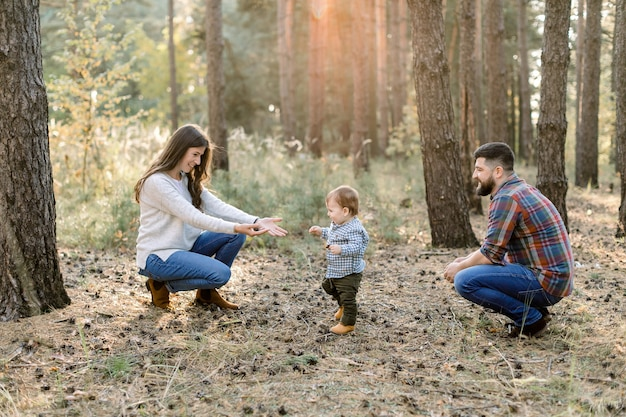 Horizontaal buiten schot van mooie jonge kaukasische familie op een wandeling in de herfstbos. kleine kind babyjongen lopen van zijn vader naar moeder en lachen