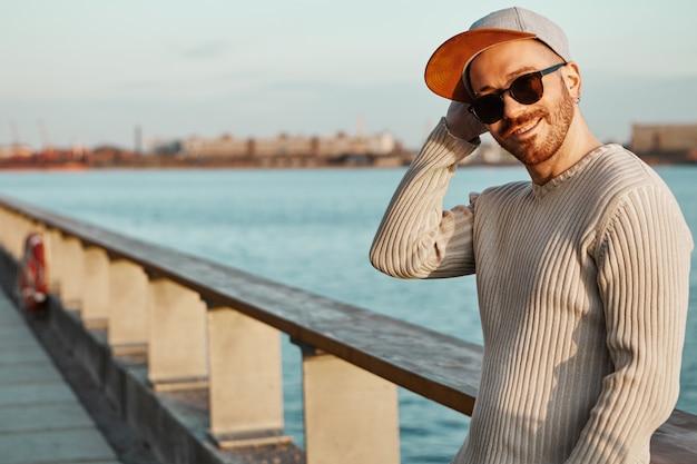 Horizontaal buitenbeeld van charmante hipster-man in tinten en snapback