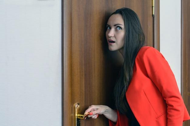 Horizontaal close-upportret van een vrouw in een rood kostuum die afluisteren, de deur van de baas bespioneren