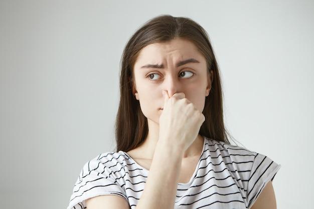 Horizontaal geïsoleerd gefrustreerd fronsende jonge donkerharige vrouw met een walgelijke blik, haar neus knijpen en de adem inhouden vanwege een onaangename walgelijke geur, geur of stank