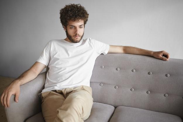 Horizontaal geïsoleerd portret van aantrekkelijke jonge blanke man met volumineus haar en dikke baard die terloops op een grijze bank thuis zit, voor zich uit kijkend, met een peinzende, doordachte uitdrukking