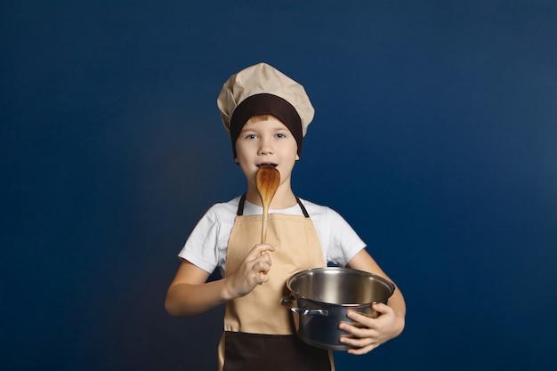 Horizontaal geïsoleerd schot van leuke 10 éénjarigen kaukasische jongen die schort en chef-kokhoed het stellen draagt