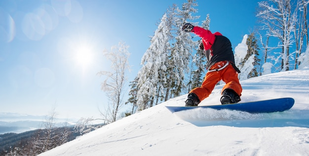 Horizontaal laag hoekschot van een mannelijke snowboarder die de helling berijdt op een zonnige de winterdag in de bergen. bos, blauwe lucht en zon.