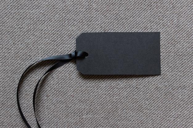Horizontaal leeg zwart papier prijsetiket op gestructureerde gestreepte stof met satijnen touw
