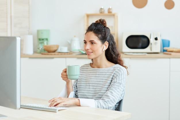 Horizontaal middelgroot portret van een jonge vrouw die haar bureaucomputer gebruikt en thuis 's ochtends koffie drinkt