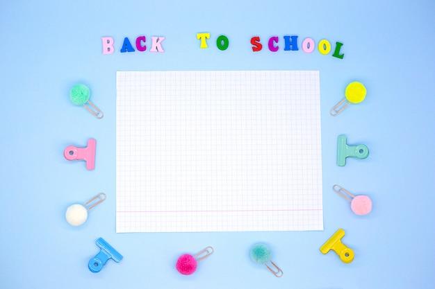Horizontaal notitieboekjeblad op blauw omringd door paperclippen en bindmiddelen naast inschrijving - terug naar school