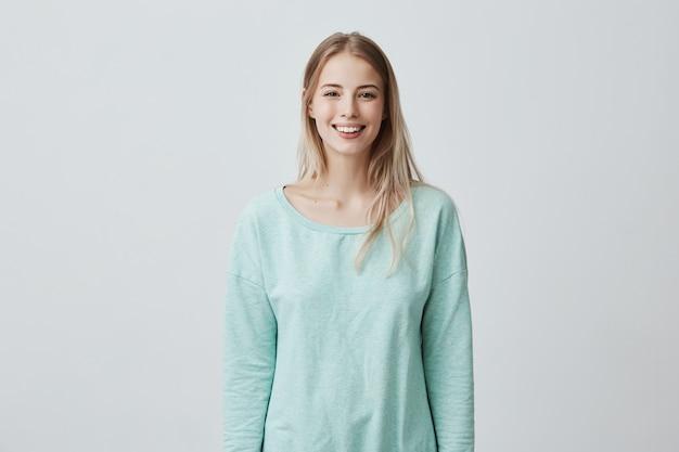 Horizontaal portret van aangenaam ogende blanke vrouw met lang blond haar, gekleed in witte casual blauwe trui, op zoek gelukkig