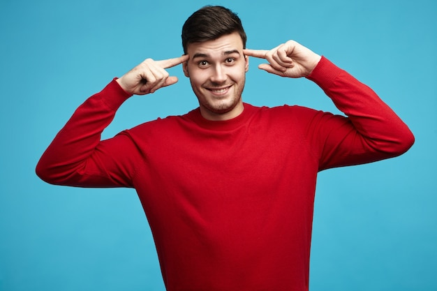 Horizontaal portret van aantrekkelijke emotionele jonge donkerharige kerel in rode sweater die voorvingers houdt