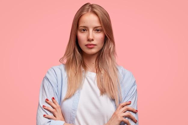 Horizontaal portret van aantrekkelijke serieuze europese vrouw houdt de handen gekruist en ziet er zelfverzekerd uit