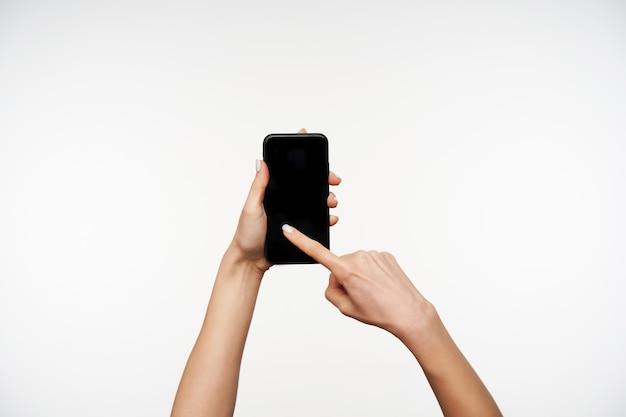 Horizontaal portret van de handen van de jonge vrouw die terwijl het houden van mobiele telefoon wordt opgeheven en met wijsvinger op scherm, die zich voordeed op wit vegen