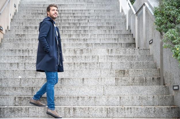 Horizontaal portret van de jonge aantrekkelijke mens die zich op stappen bevinden die terug eruit zien. moderne en stijlvolle man houdt laptop handen.