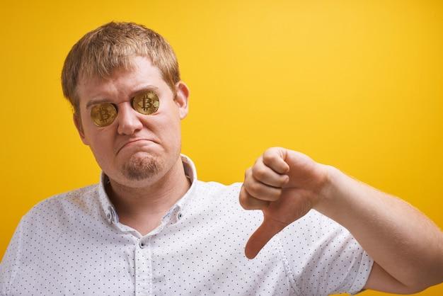 Horizontaal portret van dikke kerel met bitcoins in zijn ogen op een gele achtergrond. digitaal virtueel valutaconcept, bedrogen belegger, cryptocurrency vallen op internetmarkt