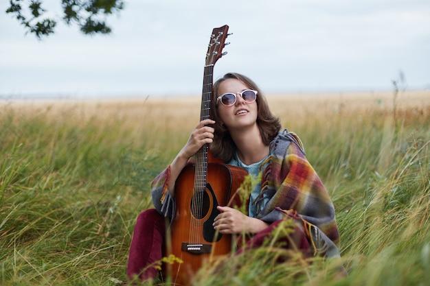 Horizontaal portret van dromerig wijfje die in zonnebril akoestische gitaar houden kijkend upwards dromend over ware liefde