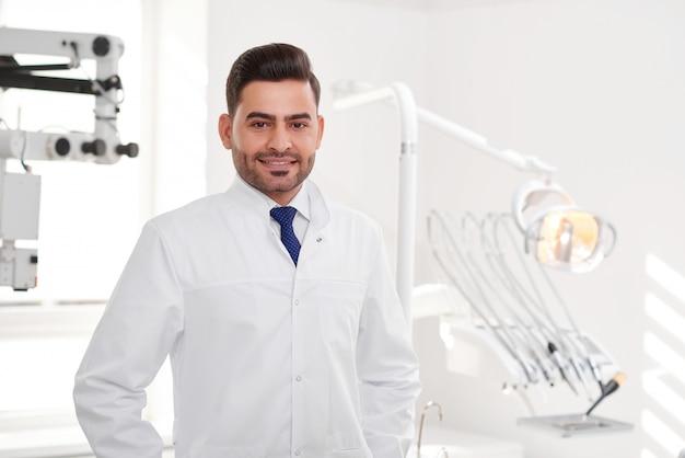 Horizontaal portret van een knappe spaanse mannelijke tandarts die zich voordeed bij zijn kliniek glimlachend vreugdevol copyspace geneeskunde tandheelkunde mensen welzijn nuttige vriendelijke gezondheid tanden mondeling concept.