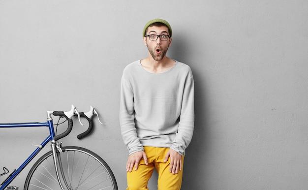 Horizontaal portret van een stijlvolle bebaarde man die een tocht met de fiets gaat maken, met een verbaasde uitdrukking kijkend nadat hij zich realiseerde dat hij alles uit deze tour zou halen