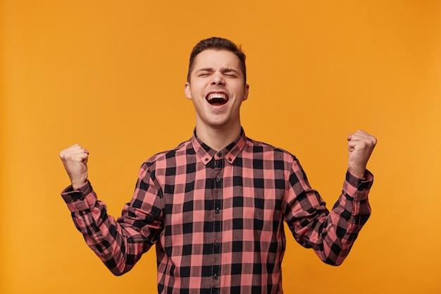 Horizontaal portret van een vrolijke, gelukkige blonde man in demim overhemd die vuisten als winnaar balde